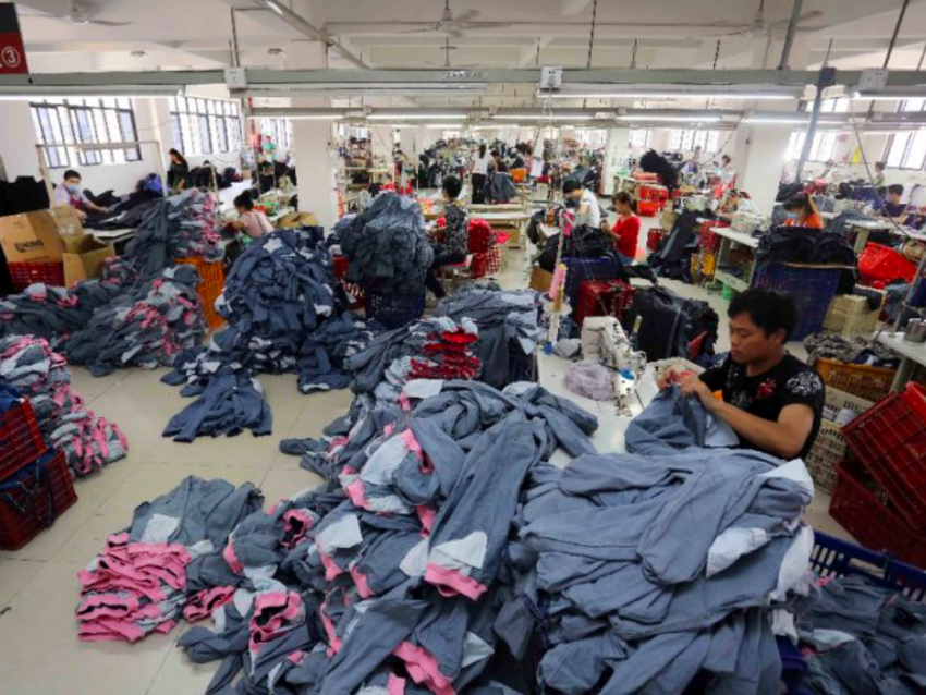 A man sits sewing in a factory. He is surrounded by the pile of garments on which he sews.